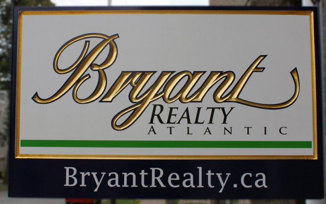 "Bryant Realty 20"" x 32"" v-carved and gilded double sided hanging sign."