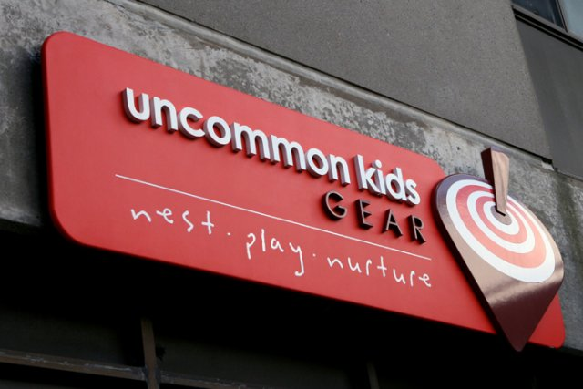 """Uncommon Kids 72"""" x 24"""" Extira backer panel with dimensional text and graphics."""