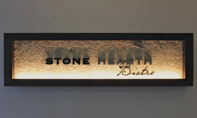 Flooding this custom wooden framed sign from the bottom casts dramatic shadows over the stone and laser cut text.