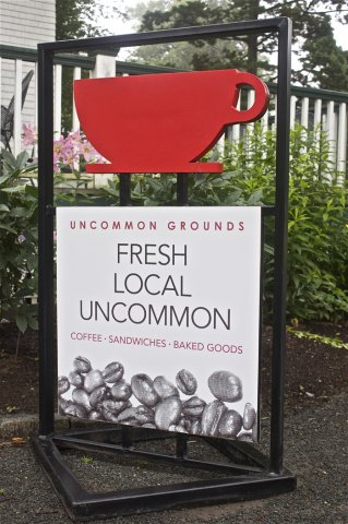 Uncommon Grounds Custom built 2' x 4' pylon sign with dimensional replica of logo painted to match brand specifications. Vinyl graphic text on aluminum composite backer panel.
